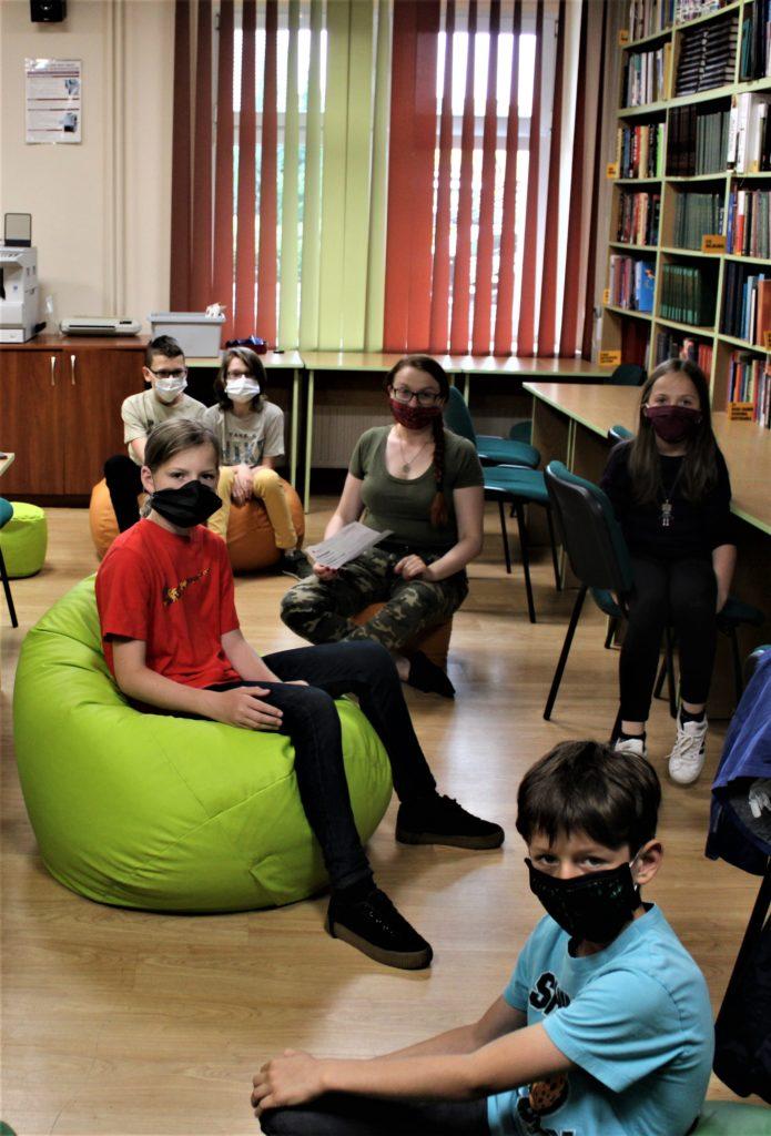 Zdjęcie przedstawia grupę dzieci w maseczkach z tabletami i robotami Photon