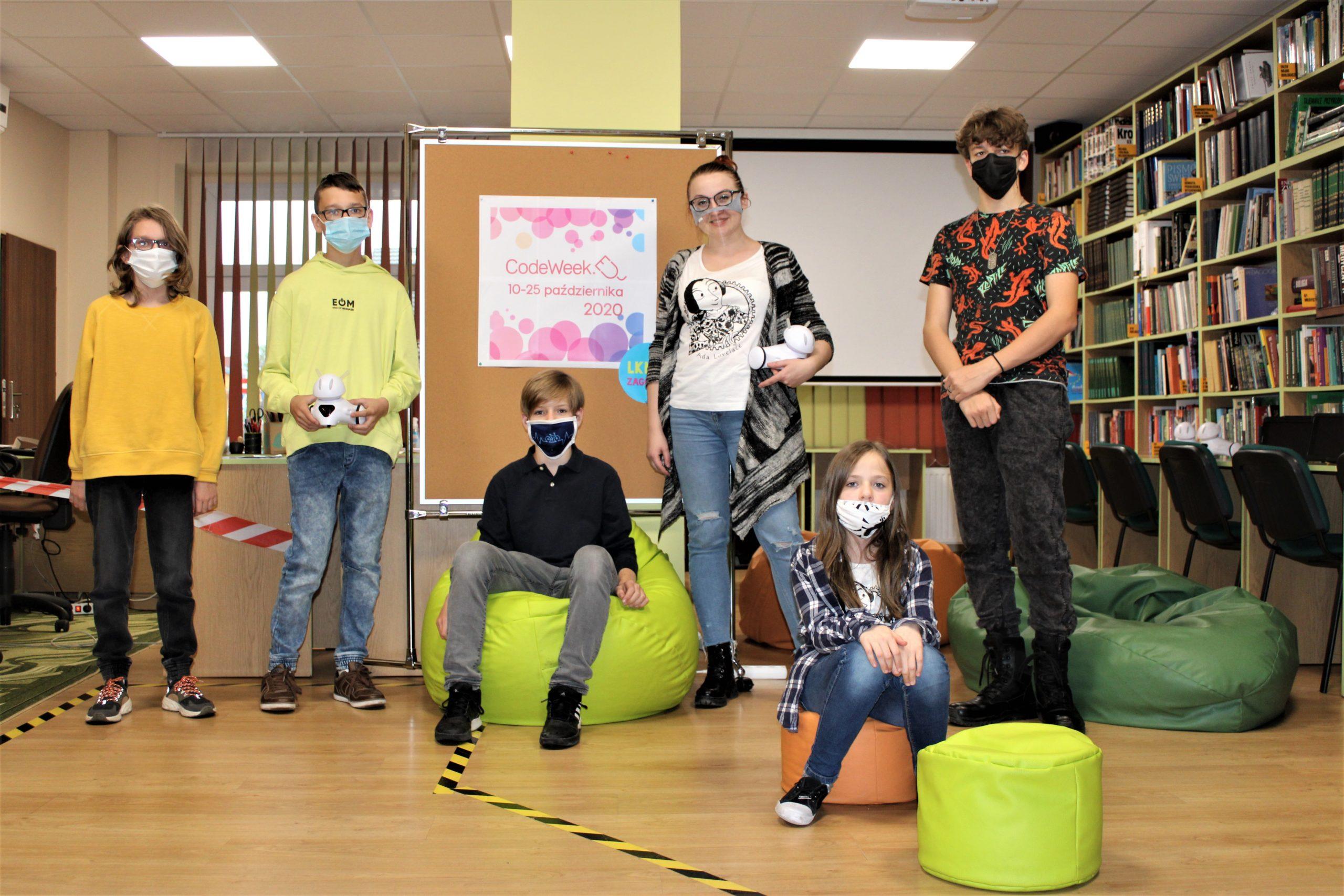 Na fotografii grupa dzieci biorących udział w zajęciach programowania robotów wraz z bibliotekarką. Dwie osoby trzymają w rękach roboty.