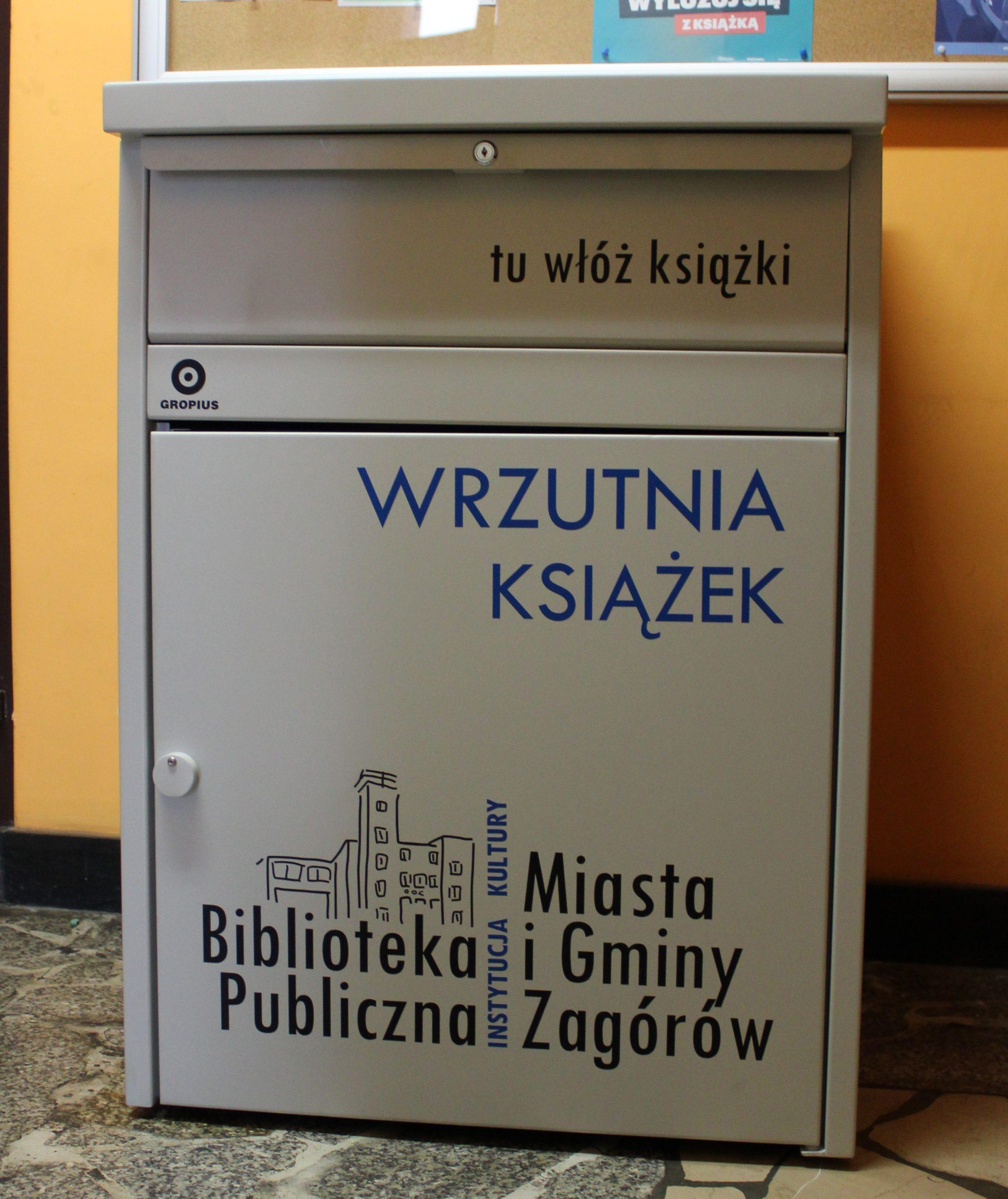 """Na zdjęciu wrzutnia do książek, stojąca przed drzwiami wejściowymi do biblioteki. Pojemnik szary, z naklejonym logo i napisem: wrzutnia książek. Szuflada wrzutni oznaczona jest napisem : """"tu włóż książki""""."""