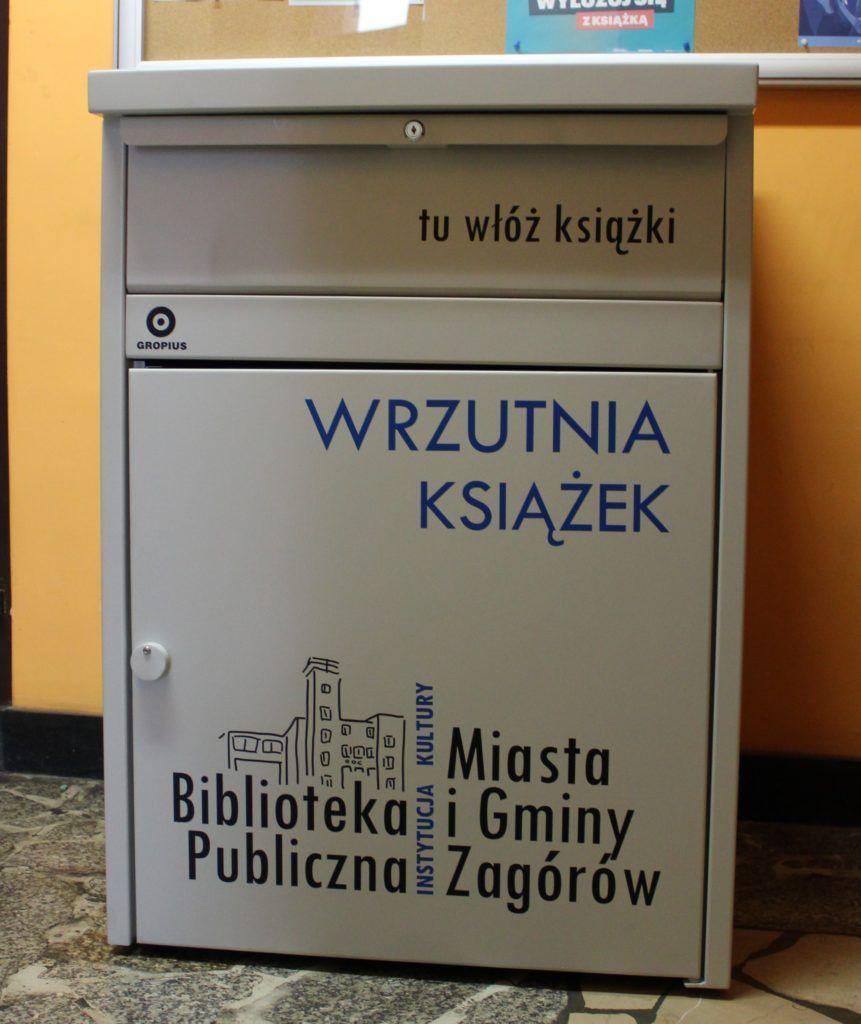 Na zdjęciu wrzutnia do książek oznaczona logo biblioteki i opisana. W górnej części szuflada z napisem : tu włóż książki