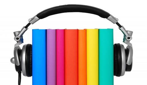 Na zdjęciu książki stojące grzbietami do obserwującego. Na książki jak na głowę nałożone są słuchawki nauszne