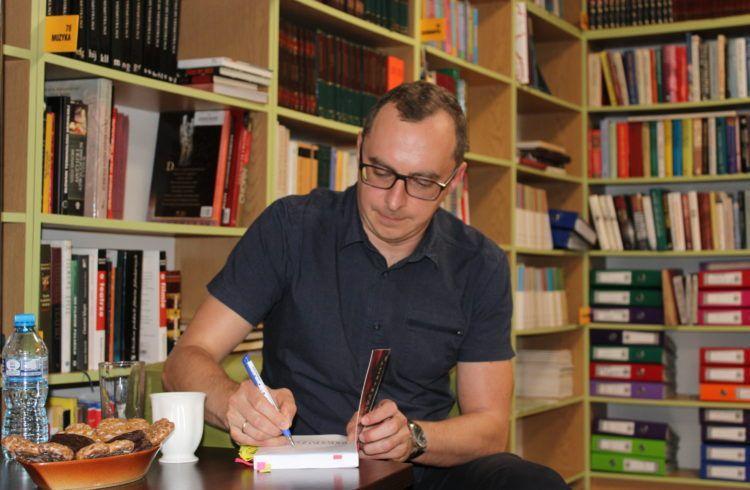 Mężczyzna w okularach pochyla się nad książką, wpisując dedykację . Obok niego, na stoliku, stoi biały kubek z herbatą i talerz z piernikami. Na drugim planie, w tle - regały z ksiażkami.