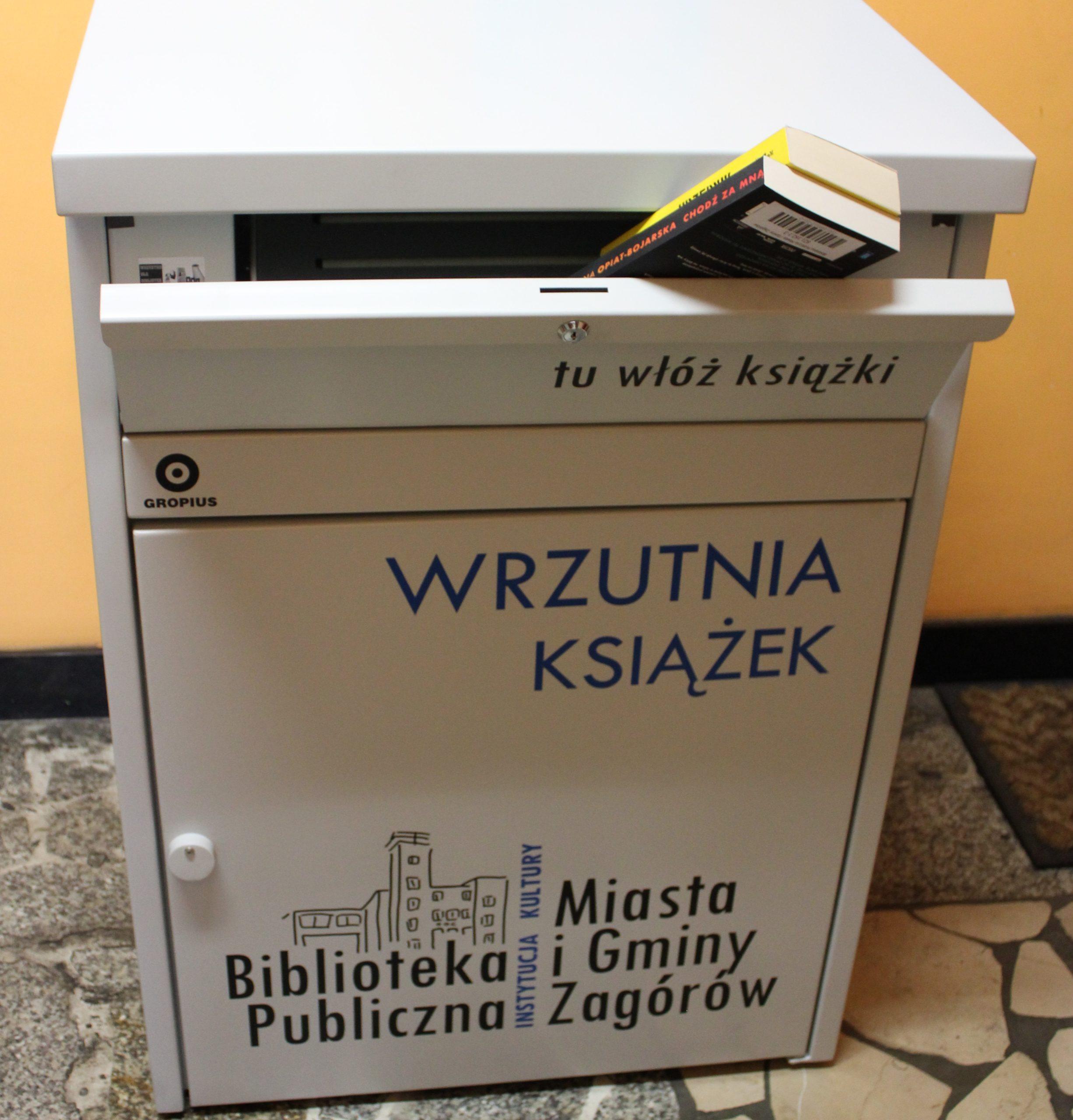"""Na zdjęciu wrzutnia do książek, stojąca przed drzwiami wejściowymi do biblioteki. Pojemik szary, z naklejomym logo i napisem: wrzutnia książek. W uchylonej szufladzie z napisem : """"tu włóż książki"""" są wyeksponowane dwie książki. Pokazuje to sposób użycia wrzutni."""