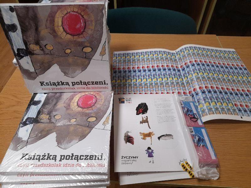 """Na zdjęciu książki wchodzące w skład """"wyprawki czytelniczej"""" i zestaw naklejek, kart do zbierania naklejek"""