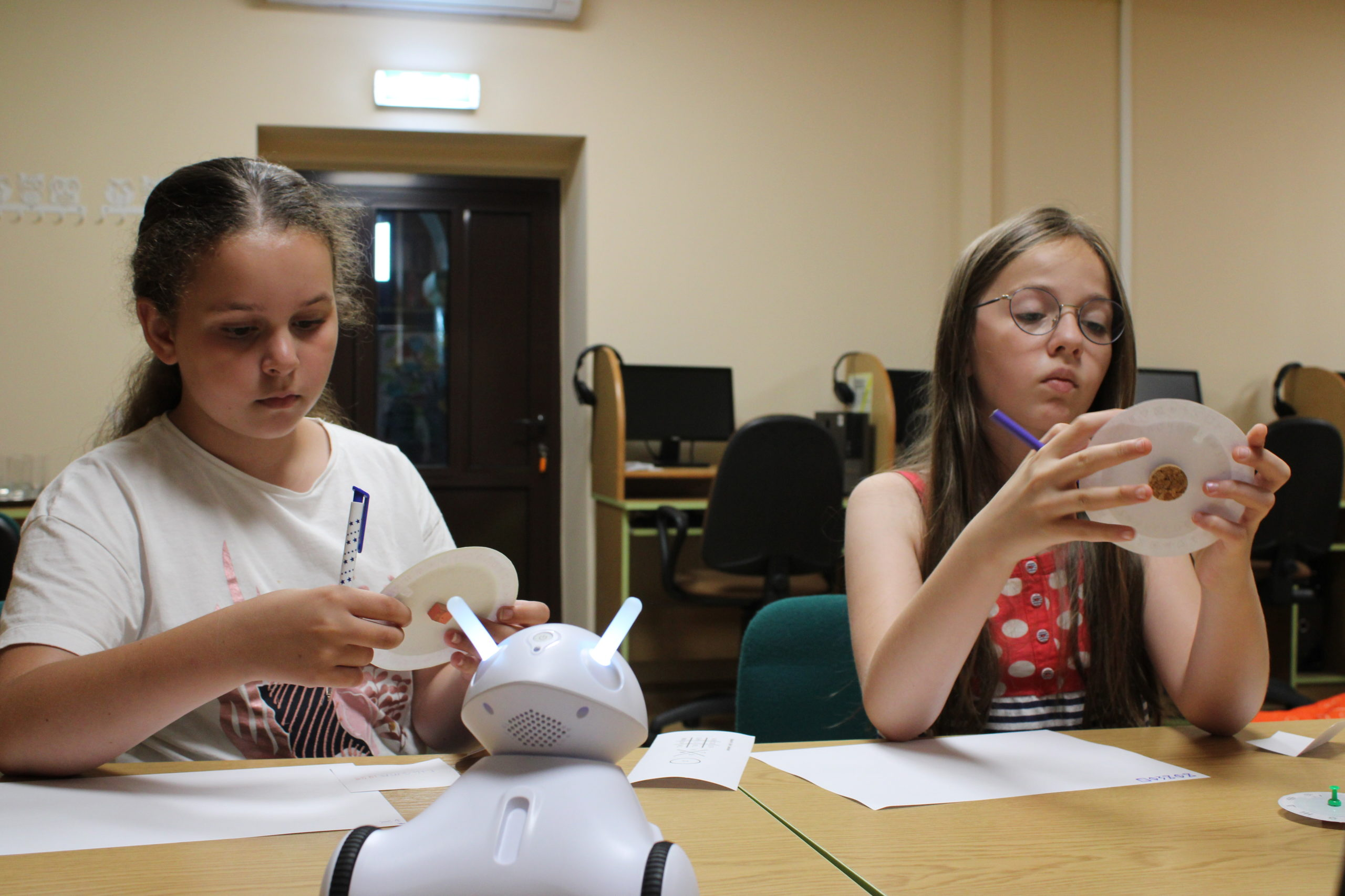 Na pierwszym planie robot Photon ( przypomina białego królika na czarnych kołach, ze świecącymi czółkami i oczkamia ), na drugim planie dwie dziewczynki , zajmujące się rozszyfrowywaniem zakodowanych wiadomości. Obie dziewczynki trzymają w dłoniach dyski szyfrujące przygotowane z tektury i długopisy, którymi będą zapisywać informacje na kartkach papieru.