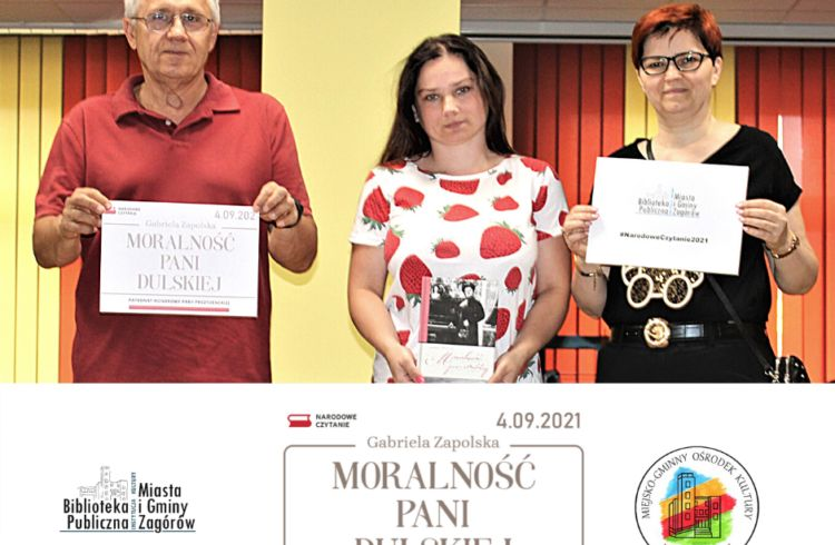 """Na plakacie widać trzy osoby. Od lewej :siwowłosy mężczyzna w okularach, w czerwonej koszulce polo trzymający w dłoniach kartkę z napisem """"Moralność pani Dulskiej. Narodowe Czytanie 4.09.2021"""", ciemnowłosa kobieta w jasnym tiszercie w truskawki, trzymająca przed sobą egzemplarz książki """"Moralność pani Dulskiej"""" Gabrieli Zapolskiej oraz rudowłosa kobieta z krótkimi włosami, w ciemnym stroju i w okularach, prezentująca kartkę z logo Biblioteki Publicznej Miasta i Gminy Zagórów oraz hasztagiem #NarodoweCzytanie2021."""