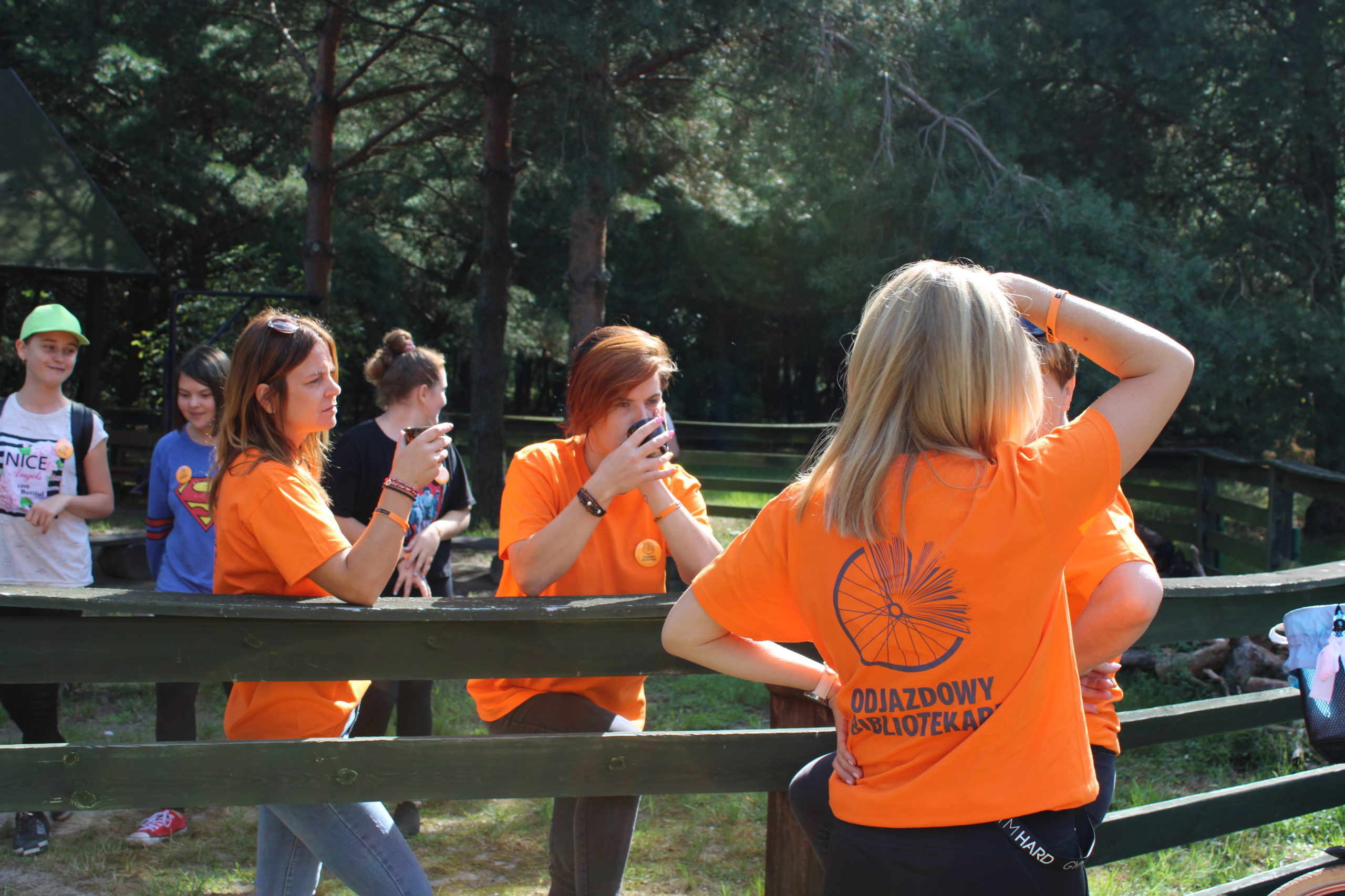 Na pierwszy planie blondynka, ubrana w pomarańczową koszulkę z napisem Odjazdowy Bibliotekarz, stoi plecami do obiektywu i spogląda przed siebie, osłaniając oczy przed słońcem uniesioną dłonią. Na drugim planie dwie inne kobiety w pomarańczonych koszulkach z logo, oparte o drewniany płot, trzymają w dłoniach kubki z kawą. Na trzecim planie trzy dziewczynki ,roześmiane. Krajobraz leśny, drzewa, dużo zieleni.